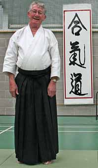 Foster Sensei standing in front of                                 Aikido kanji