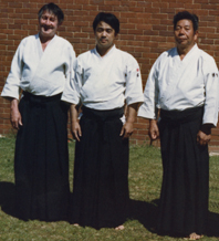 3                                             Sensei: Foster, Tomita and                                             Saito standing together                                             outside